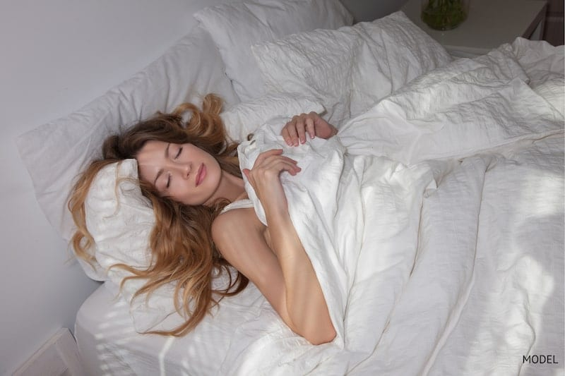 Woman sleeping on her back in her bed comfortably.