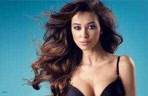 Young brunette woman with full hair and shapely breasts standing in a black bra against a blue background.
