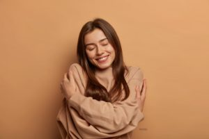 Woman wrapping arms around herself, showing self-love