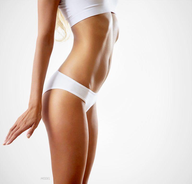 Profile of slim woman wearing white undergarments.